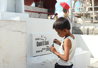 PAINTWORK.  A young boy in Tibungco Public Cemetery offers to repaint the carved writings of a gravestone for a modest fee.  (davaotoday.com photo by Medel V. Hernani)