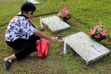 CANDLE OFFERING.  A woman lights candles at the tombstone of her dear departed in Matina village's Davao Memorial Park.  (davaotoday.com photo by Medel V. Hernani)