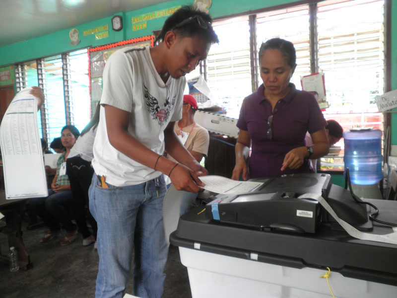 TRY & TRY.  A voter in Panabo City attempts to feed the ballot to the PCOS machine five times, to no avail.  (davaotoday.com photo by Mart D. Sambalud)