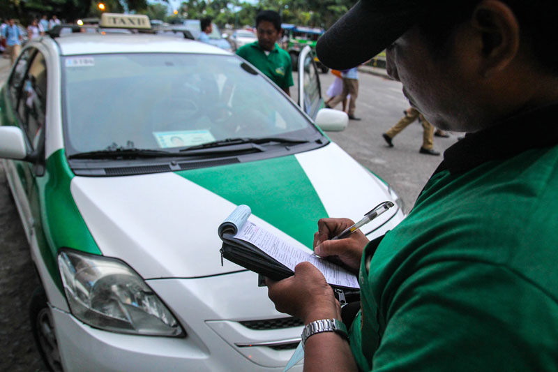 ALARM.  A traffic enforcer in Davao City issues a violation ticket against a cab driver for illegal terminal, when he parked his vehicle outside the school along Roxas Street.  (davaotoday.com photo by Ace R. Morandante)