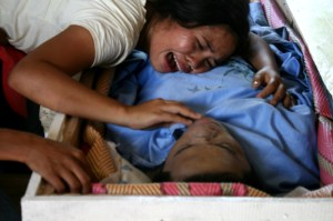 Sister of Benjie Planos, slain leader of the Agusan Manobo group, wails and clings to his body during his burial on Tuesday. Planos' murder comes weeks after the Manobos returned to their community after an agreement to stop militarization in their community in Loreto, Agusan del Sur. The Manobos pin his murder on paramilitary and soldiers. (davaotoday.com photo by Earl O. Condeza)