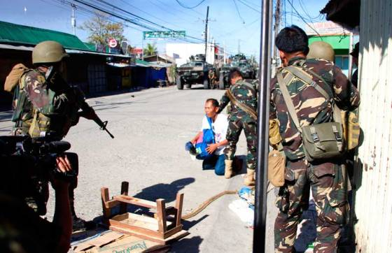 A government soldier takes ready aim at a Zamboanga civilian while his comrade holds the latter down. The person came out of Lustre Street where government troops were pursuing off MNLF rebels.  (davaotoday.com photo by John Rizle L. Saligumba)