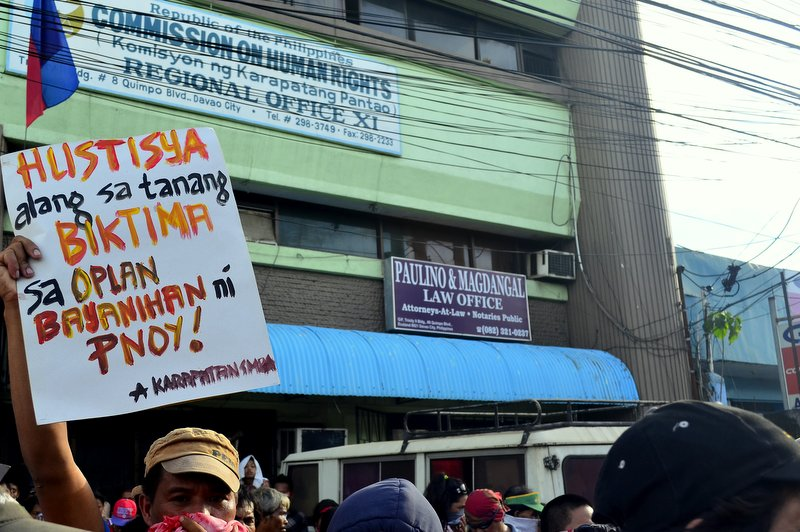 MESSAGE FOR CHR One of the protesters raises his placard during a picket on Tuesday at the office of the Commission on Human Rights, demanding for investigation of victims of extrajudicial killings. (davaotoday.com photo by Earl O. Condeza)
