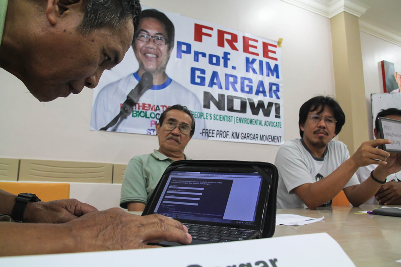 FATHER'S SUPPORT Emmanuel Gargar (left), father of detained scientist Professor Kim Gargar, types his name on a website created by Kim's colleagues and rights advocates calling for his release.  Kim Gargar was conducting post-Typhoon Pablo studies in Cateel, Davao Oriental when he was detained and charged by the military that he is a New People's Army member.  (davaotoday.com photo by Ace R. Morandate)