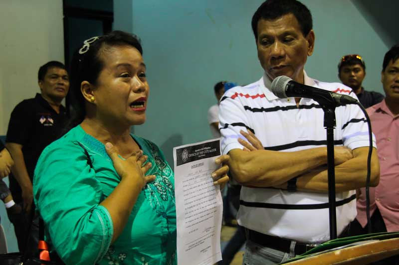 TACLOBAN OFFICIAL THANKS DUTERTE An elected barangay official from Tacloban, Leyte, Jessica Seno Panis (left) cries as she thanks Davao City Mayor Rodrigo Duterte (right) for including her during Friday's oath taking ceremony of new barangay officials at Almendras Gym.  Panis is temporarily residing with relatives in Davao after Typhoon Yolanda ravaged her city and other parts of Eastern Visayas, but said she will return soon to serve her constituents in Barangay 73 PHHC. (davaotoday.com photo by Ace R. Morandante)