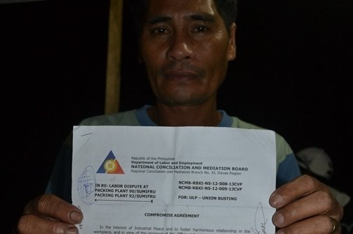 Namasufa union president Vicente Barrios shows the memorandum of agreement between Sumifru management, contract growers and union officials granting the return to work with back wages of 141 workers. (contributed photo)