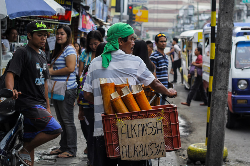 Amidst tough times, a vendor in a bicycle calls for everyone to save money through his bamboo-made alkansya.