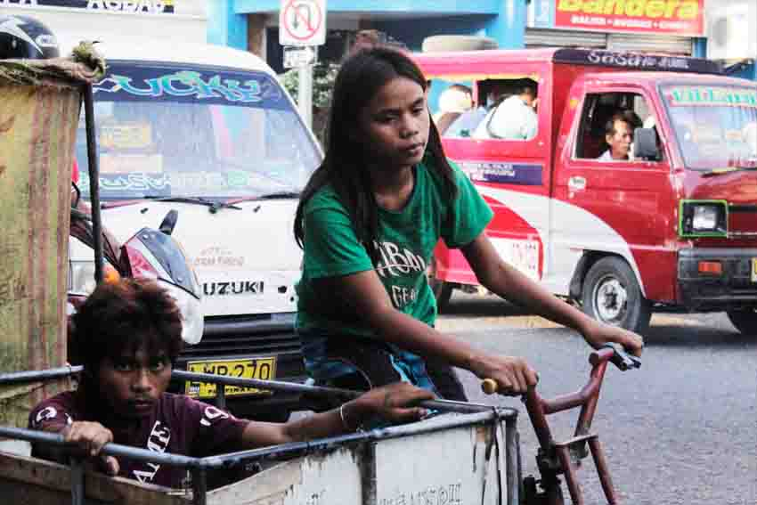 It's an exhausting day for this young girl who bikes off with her brother looking for useful trash as they navigate the tight road along C. Bangoy corner Palmagil, Davao City.