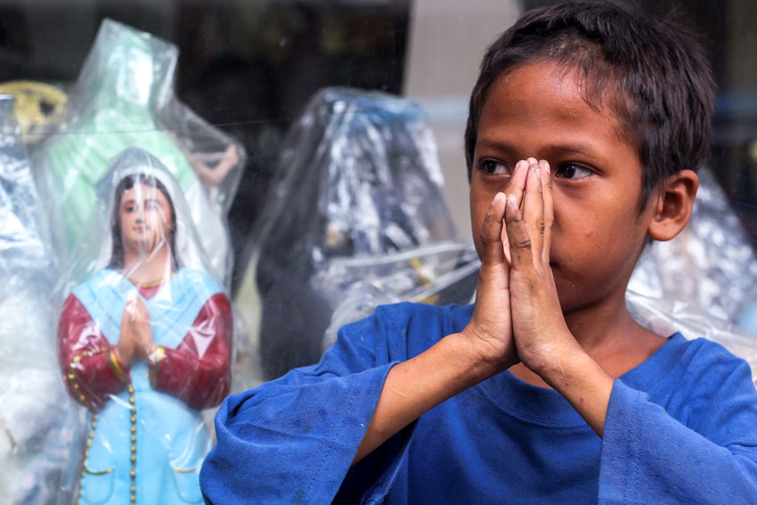 POTRAYING IMAGE. A street child mimics a religious statue displayed along downtown Bolton street of Davao City. (Ace R. Morandante/davaotoday.com)