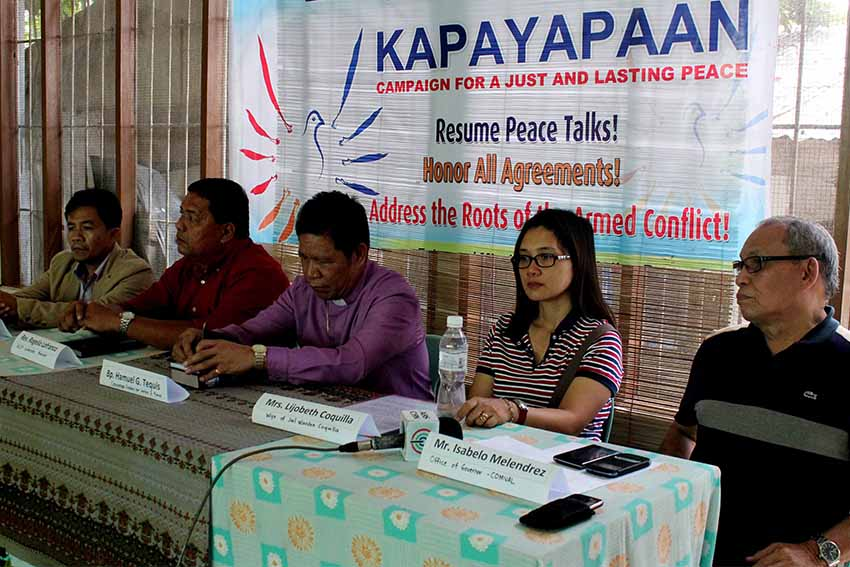 Lijobeth Coquilla, wife of NPA captive jail warden Jose Mervin Coquilla, appeals for the release of her husband Thursday. She is accompanied by Compostela Valley Province executive assistant Isabelo Melendrez and peace group Exodus for Justice and Peace. (Medel V. Hernani/davaotoday.com)