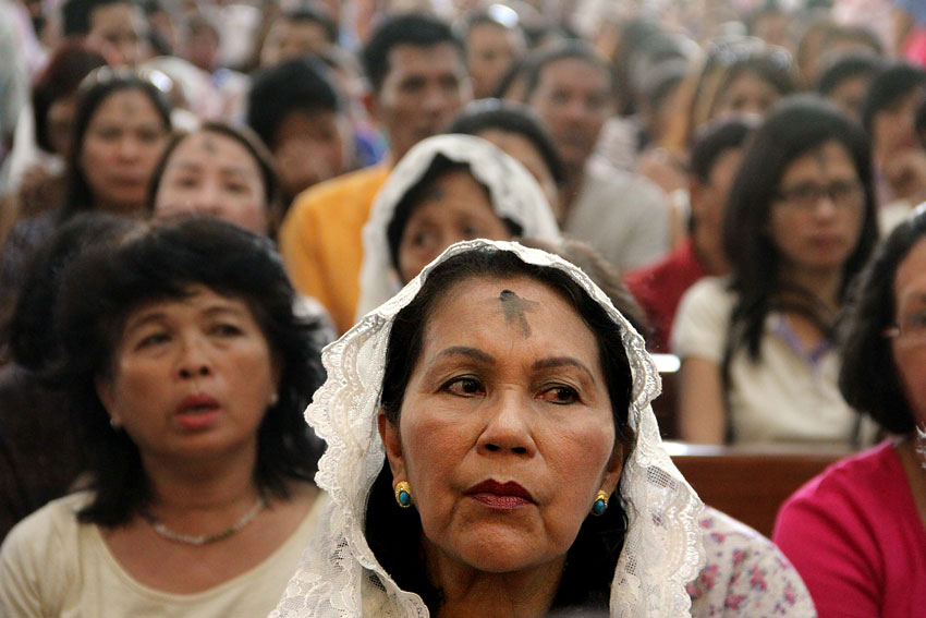 A devotee listens to the sermon of Bishop Romulo  Valles after putting an ash cross sign on her forehead along with thousands of devotees at San Pedro Cathedral, Wednesday. (Ace R. Morandante/davaotoday.com) >