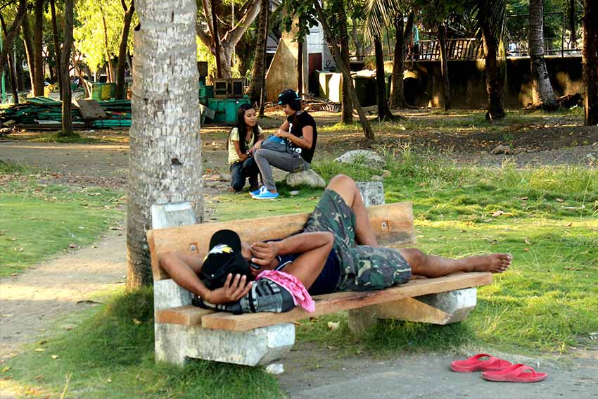 A man busies himself with his mobile phone, while a couple takes photographs of each other at Magsaysay Park. (Medel V. Hernani/davaotoday.com)