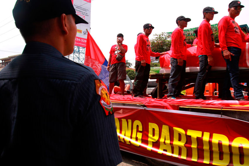RED GUARDS. A police officer watches the coffin of New People's Army commander Leoncio Pitao, alias Kumander Parago, as Red guards surround the coffin displayed along the highway of Buhangin, Davao City during the funeral caravan.(Ace R. Morandante/davaotoday.com)