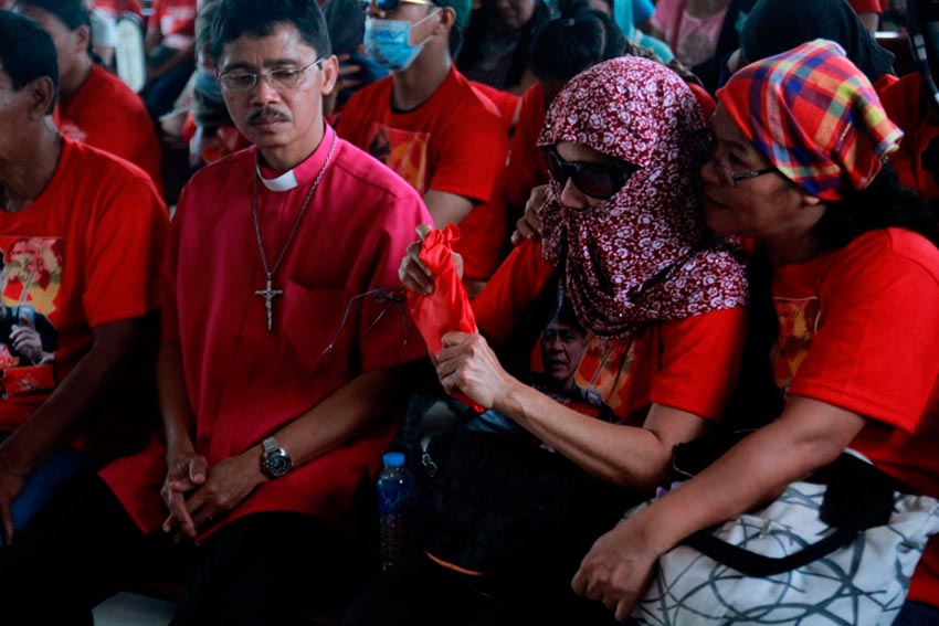 WIFE. Evangeline, wife of slain NPA commander Leoncio Pitao, receives the flag of the Communist Party of the Philippines after the liturgy held at the chapel inside Davao Memorial Park. Beside her is Bishop Jonathan Casimina of the Episcopal Diocese of Davao.(Ace R. Morandante/davaotoday.com)