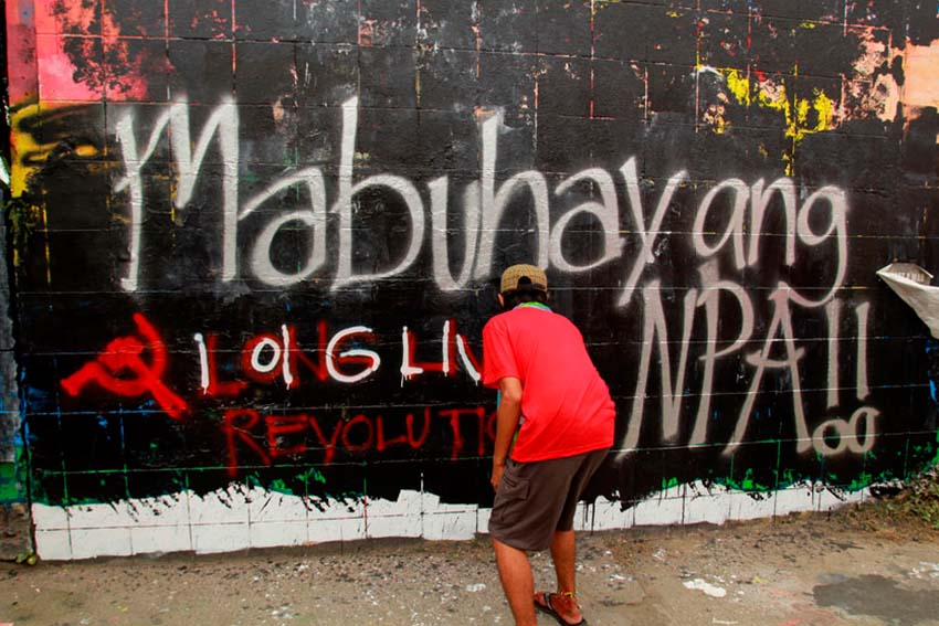 REPAINT. Members of the underground youth movement repaint the graffiti wall along Matina highway in Davao City with images of Kumander Parago and the words Long Live the New People's Army. On Thursday afternoon local artist finished a mural of Kumander Parago, however it was defaced in black paint immediately.(Ace R. Morandante/davaotoday.com)