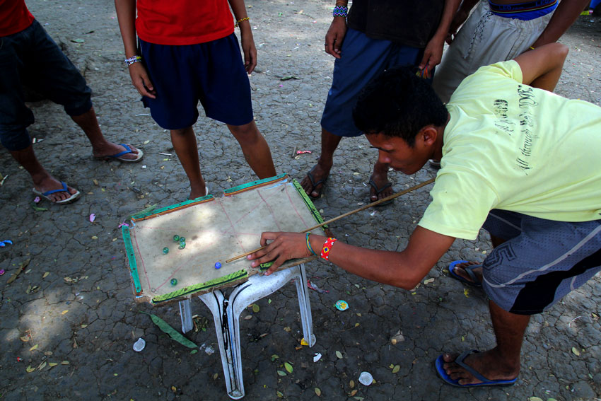 Manobo evacuees play billiards using marbles and a mini board inside a church compound here where they have been staying for the last five months. (Ace R. Morandante/davaotoday.com)