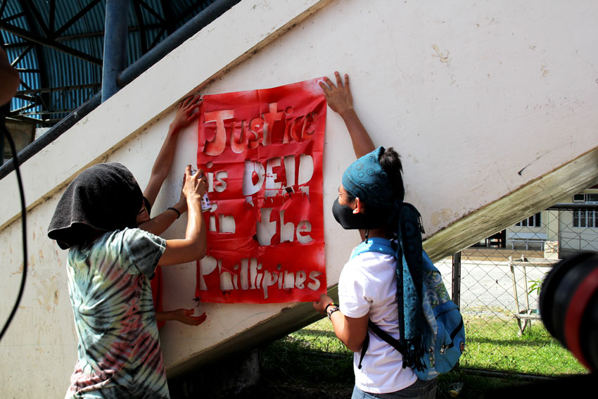 "Protesters paint the words ""Justice is dead in the Philippines"" during the funeral caravan of Emerito Samarca."