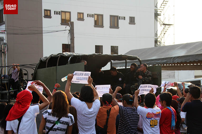 "A group of activists gets close to an Army truck full of soldiers while shouting ""berdugo (butchers)"" after a visit of President Benigno Aquino III in Davao City. The group held a protest several meters away from a school where Aquino visited to demand justice for the killings of Lumads in Mindanao. (John Rizle L. Saligumba/davaotoday.com)"