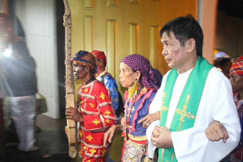 INTERFAITH.​ Father Teody Holgado, head priest of Baclaran church, links arms with Mindanao's first woman chieftain (center) along with other Lumad leaders in Pasay City, Sunday evening. The Lumads are in Manila to campaign against Lumad killings and to call for the pull out of military troops from their communities. (Earl O. Condeza/davaotoday.com)