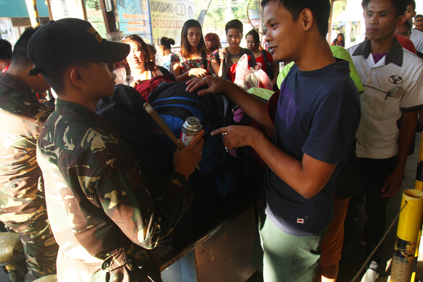 TERMINAL. A commuter is reprimanded by an officer of the Task Force Davao after being caught bringing a bottle of butane gas during the inspection at the entrance of Davao City Overland Transport Terminal in Ecoland. (Ace R. Morandante/davaotoday.com)