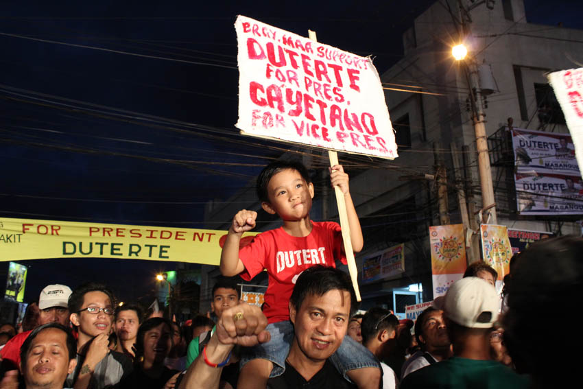 This father and son pose for the camera while waiting for Mayor Rodrigo Duterte and his the running Peter Cayetano for Vice President on stage.(Medel V. Hernani/davaotoday.com)