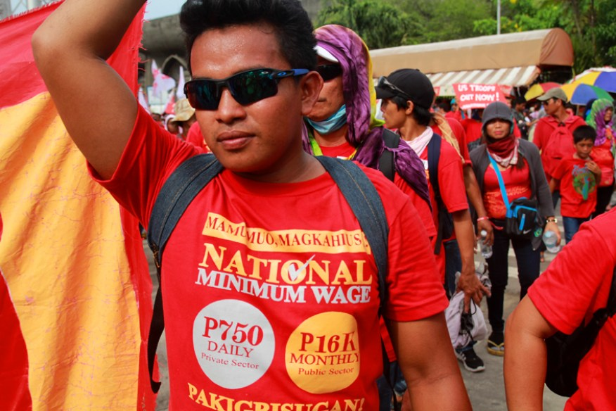 Workers wear shirts with their calls to raise the national minimum wage to P750 for the private sector and P16,000 for the public sector.