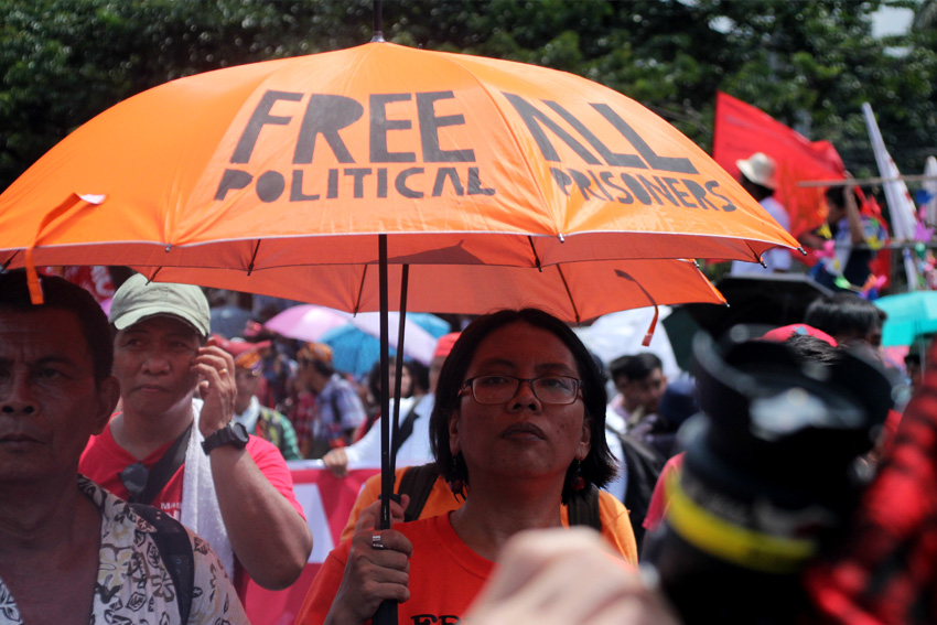 Christina Palabay, spokesperson of human rights group Karapatan, bring an umbrella with their call to free all political prisoners.