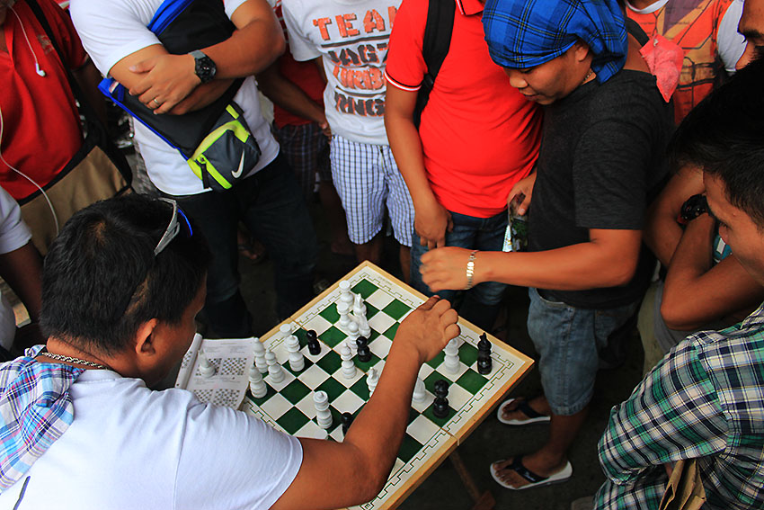 CHESS MATCH. Passersby converge and place their bets on a chess match being played on one of the sidewalks in San Pedro Extension, Davao City. (Paulo C. Rizal/davaotoday.com)