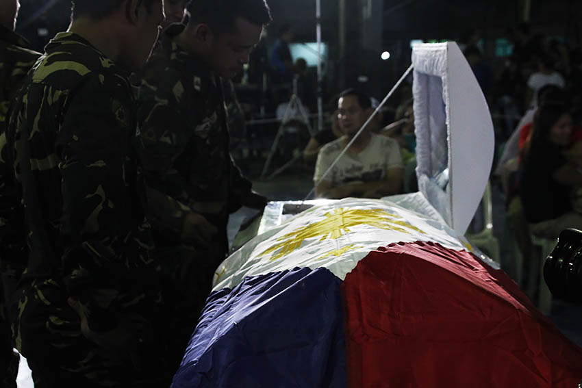 KILLED IN ACTION. Soldiers look on at the corpse of Pfc. Rolen Roy C. Sarmiento, one of the soldiers who died in a series of offensives by the 8th Pulang Bagani Company of the New People's Army in Monkayo Town, Compostela Valley. Sarmiento, along with three others are currently laid at state at Camp Apolinario, in Panacan, Davao City. (Paulo C. Rizal/davaotoday.com)