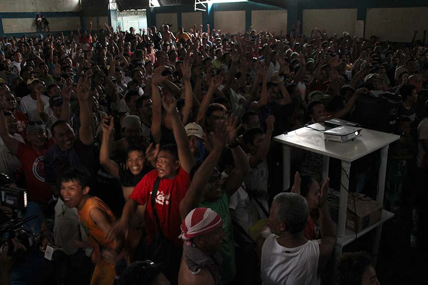 ELATED FANS. Hundreds of supporters inside the Bangkerohan Multi-purpose gym in Barangay 5-A, Davao City jump with joy as boxing champ Manny Pacquiao scores a unanimous decision over Jessie Vargas.  Pacquaio, who is also a Senator, claims the World Boxing Organization welterweight title in Las Vegas on Sunday afternoon, Nov. 6. (Paulo C. Rizal/davaotoday.com)