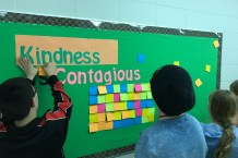 "Students collaborate to represent the idea of kindness using the ""enabling constrain"" of a sticky note mosaic."
