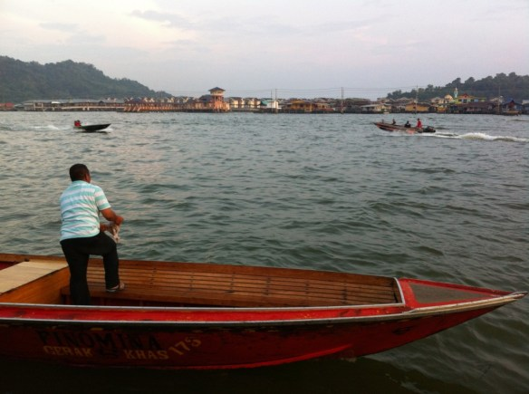 Prepping the boat for departure. Kampung Ayer in the backgorund.