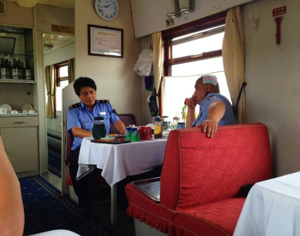 Train police having a meal and a towel on the head to cool off.. why not?