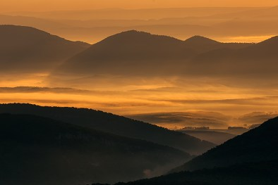 Early morning sunlight paints the misty valley