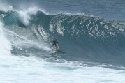 Photo of David Sills - Surfer-Saxophonist standing tall riding left at base of large wave