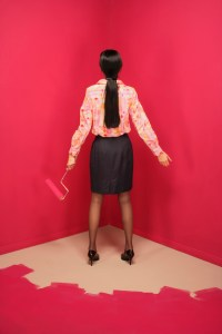 Rear view of a young woman holding a paint roller