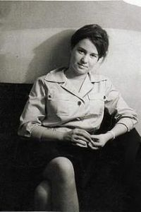 A Black & White photo of a Ulrike Meinhof in her youth, sitting in a couch looking towards the camera.