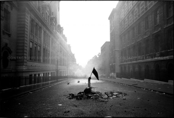 A Black & White picture oh a hand graspind a small black flag, rising from an erupting steet.