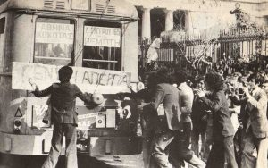 "A Black and White photo of students occupying the Polytechnic University standing in front of a Tram. A sign for ""General Strike"" is displayed."