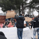 Stranded refugees facing Greek riot police chant, 'We are not terrorists!'