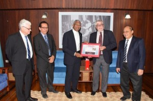 """President David Granger receives a copy of the book """"Hand-in-Hand History of Cricket in Guyana 1865-1897"""" from the insurance company's board member Mr. John Carpenter"""