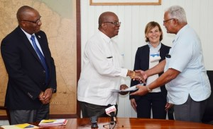Minister of Finance Winston Jordan handing over the agreement to Minister of Agriculture, Noel Holder in the presence of Minister of State, Joseph Harmon.