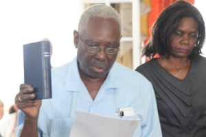 Oscar Clarke, holding the Holy Bible, as he took the Oath of Office as a councillor for the City of Georgetown.