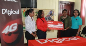 Digicel's Communications Manager, Vidya Bijlall-Sanichara and Digicel's Sponsorship Executive, Luanna Abrams  present the symbolic GYD$2 million cheque to GuyExpo's Chairperson, Dawn Holder-Alert and GuyExpo's Coordinator, Tameca Sukhdeo-Singh.
