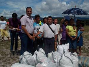 Phillipai Distribution - GF Volunteer Neil Bacchus handing over clothing to the village councilor