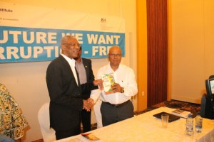 """Former Auditor General, Anand Goolsarran presenting a copy of his book """"Governance, Transparency and Accountability"""" to President David Granger."""