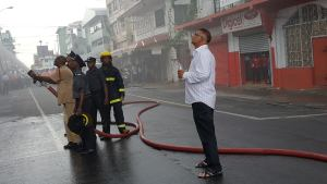 The owner of the building, Doerga Persaud, looking on as fire fighters tried their best to extinguish the blaze that engulfed his building at America Street and Avenue of the Republic.