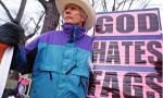 """Fred Phelps mit einem Schild auf dem """"Gott hasst Zigaretten"""" steht."""