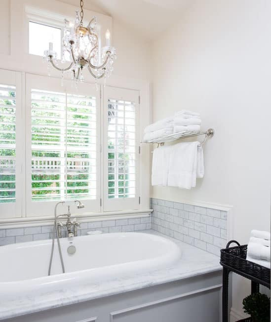 Light and bright bathroom with an enclosed tub marble slab surround