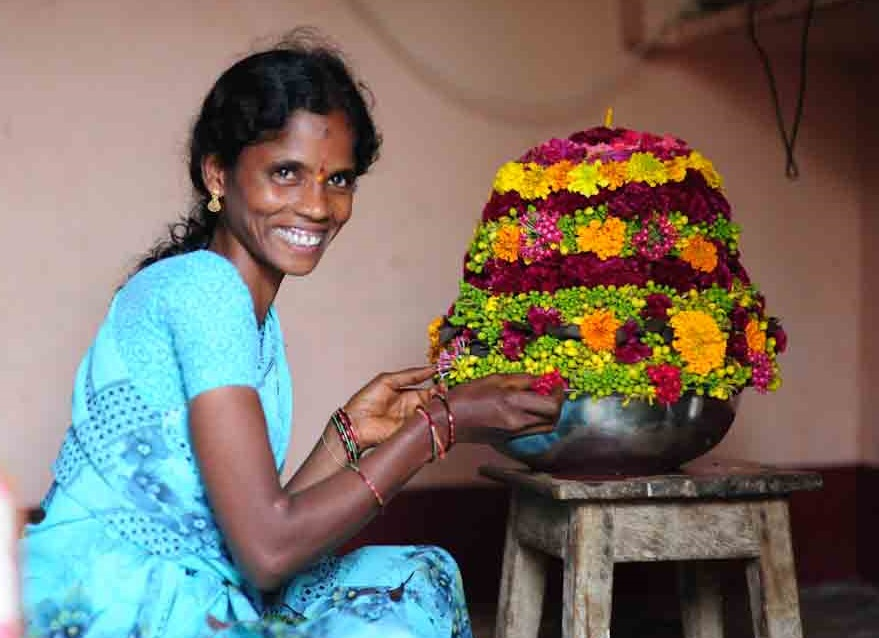 A woman smiling with Bathukamma Flower arrangeement